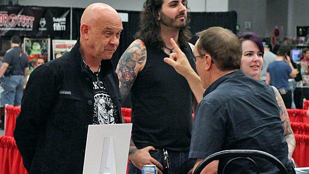 Doug Bradley (à gauche), Jeffrey Combs (à droite) et un inconnu qui se fait pointer la pomme d'Adam...