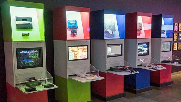Plusieurs consoles sont exposées dans une vitrine, juste au-dessus d'autres consoles mises à la disposition des visiteurs.